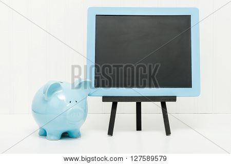 Blue porcelain piggy bank beside a blank chalkboard. Ample copy space.