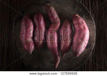 Raw sweet potatoes on wooden background.(dark style)