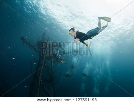 Woman diving on a breath hold near the ship wreck