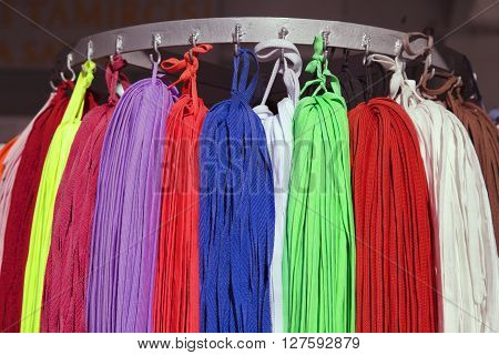 Many colorful shoestrings hanging on a rack