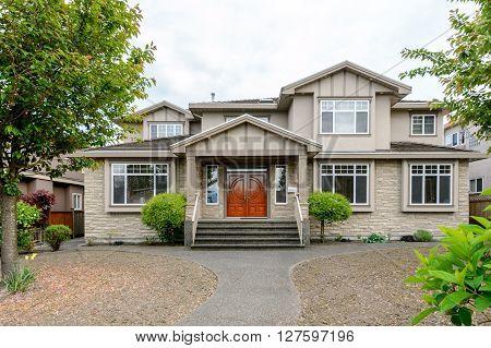 Luxury beige house with a big wooden door. Home exterior.