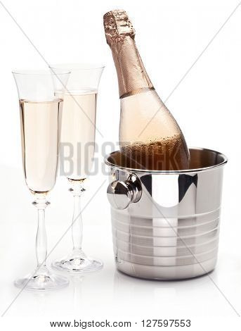 Bottle of champagne in the cooler and two glasses near it.  White background.
