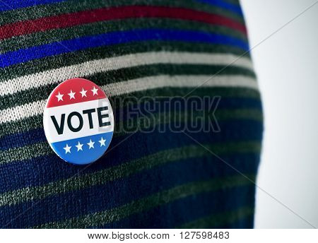 closeup of a vote badge for the United States election pinned in the sweater of a young man