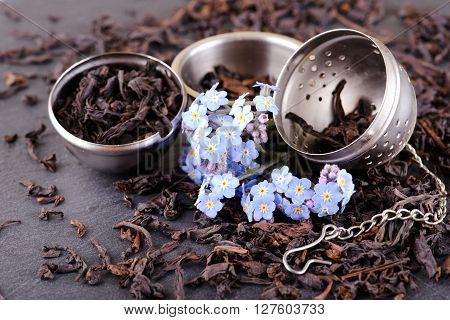 Opened Tea Strainer Next To Blue Flower And Tea Leaves