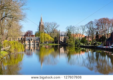 Bruges, Belgium - April 10, 2016: Spring morning in Bruges, Belgium at Lake of Love, or Minnewater, medieval houses against blue sky