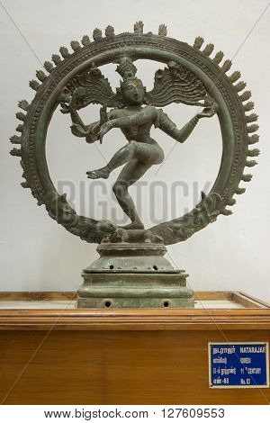 Thanjavur India - October 14 2013: Cholas era statue of dancing Lord Shiva in Nataraja pose at the Thanjavur Palace. He is captured in a see-through wheel. Hard granite placed against white wall.