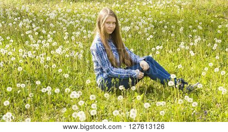 Young beautiful girl sixteen years European with long brown hair in jeans and skirt sits on meadow with white dandelions.