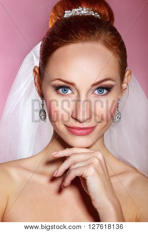 Bridal Beauty .Beautiful young woman with professional make up .Bride's portrait on a pink background.Youth and Skin Care Concept.Girl with red hair