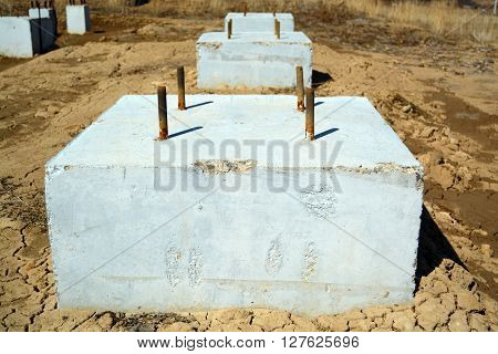 Concrete Foundation Blocks on the Ground. Concrete blocks on a wet sand ground. poster