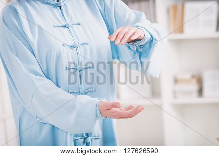 Beautiful woman doing qi gong tai chi exercise or reiki wearing professional, original Chinese clothes at home