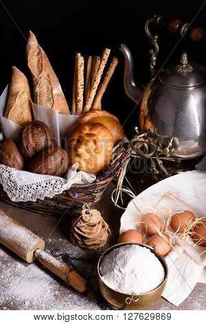 Bread, baguette, sweet pastry, bread crumbs with baking ingredients and teapot.