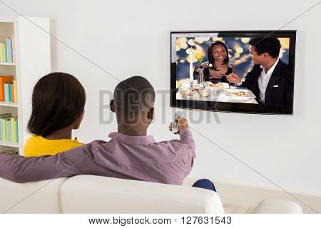 Happy African Couple Watching Television At Home