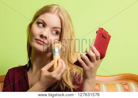 Young attractive woman applying make up with powder brush. Pretty gorgeous girl beautifying. Fashion and makeup.