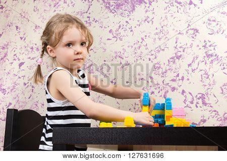 Little Girl Builds Bricks At Table