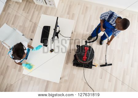 Young Male And Female Janitor Cleaning Office