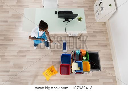Young Female Janitor Mopping Wooden Floor