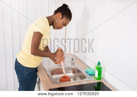 Woman Using Plunger In Sink