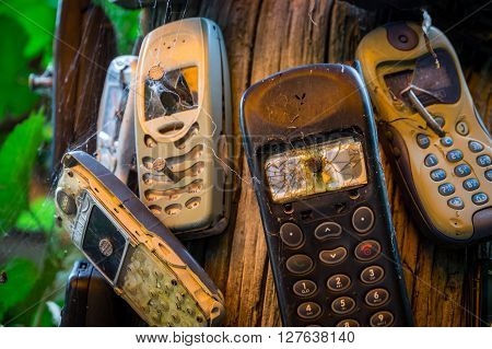 Old mobile phones are nailed to a trunk. The severely damaged mobile phones transfer the message that phones are to be turned off here.