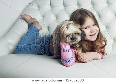 happy girl with her dog on the sofa at home