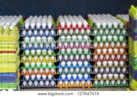 white chicken eggs in multicolored plastic boxes India