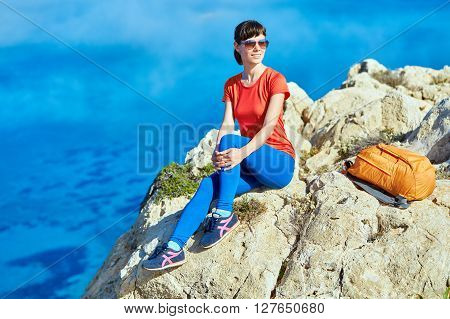 female traveler with backpack  sitting on the trail against sea and blue sky at early morning