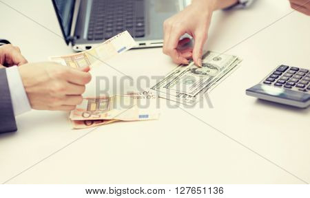 finances, currency, exchange rate, technology and people concept - close up of hands counting dollar and euro money at office
