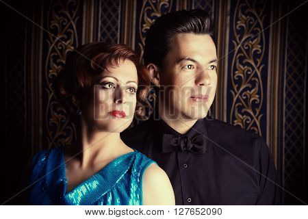 Portrait of a beautiful mature man and woman in evening clothes over vintage background.