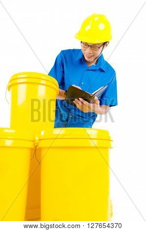 Production worker perfoming stock check on the buckets of lubricant oils and greases isolated on white background.