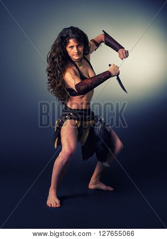 Beautiful woman in the image of a barbarian woman warrior performing a ritual dance with a knife.