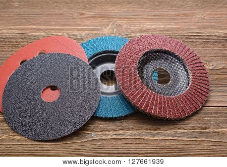 Abrasive wheels isolated on wooden background in studio
