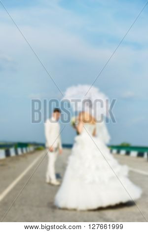 groom and bride with umbrella are on the highway on a sunny summer day. blurred