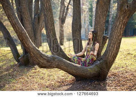 Hippie girl sitting among the tree branches