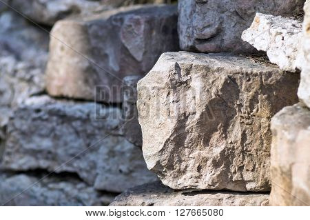 big piece of a stone closeup on an indistinct background from other stones