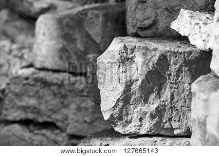 big piece of a stone closeup on an indistinct background from other stones of monochrome tone