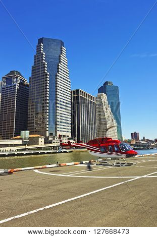 New York, USA - April 25, 2015: Helicopter landing on helipad in Lower Manhattan New York USA on East River. Pier 6. Skyscrapers on the background