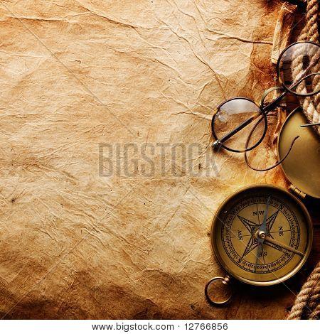 Kompass, Seil und Gläser auf Altpapier