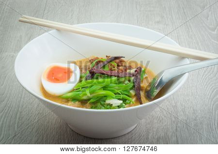 Beef noodle soup bowl with white on a wooden floor.