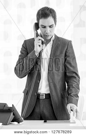 Greyscale image of a handsome young businessman standing at his desk having a conversation on a landline telephone while looking at his digital tablet.