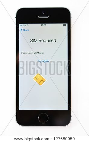PARIS FRANCE - APR 21 2016: First start of the new iPhone SE with SIm required message on screen - the new phone combines the updated processor 4K rear camera touch id retina display