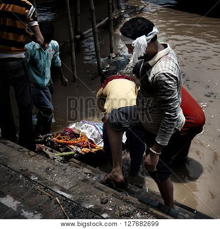 VARANASI, UTTAR PRADESH, INDIA - JULY 30: Group of Indian men bathe body of the deceased relative in Ganges river before cremation July 30, 2011 in Varanasi, Uttar Pradesh, India. It is traditional in India to cremate deceased in Varanasi, with the averag