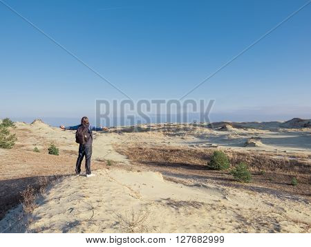 Happy man on beach spring holiday in cheerful bliss enjoying the sunshine with arms outstretched