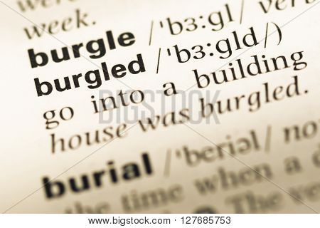 Close Up Of Old English Dictionary Page With Word Burgled.