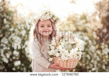 Smiling baby girl 3-4 year old holding basket of flowers outdoors. Looking at camera. Childhood.