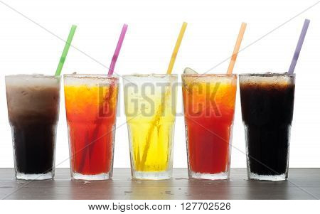 Four glasses of cold fresh homemade sodas with ice and drinking straws against a white background. Flavors include orange raspberry cola and vanilla ginger.