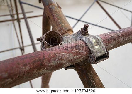 Metal scaffolding rusty joint coupler in a construction site