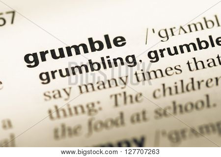 Close Up Of Old English Dictionary Page With Word Grumble.