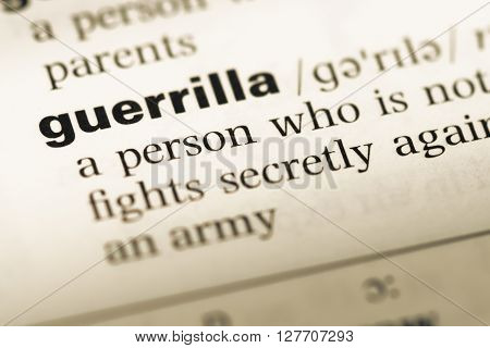 Close Up Of Old English Dictionary Page With Word Guerrilla.