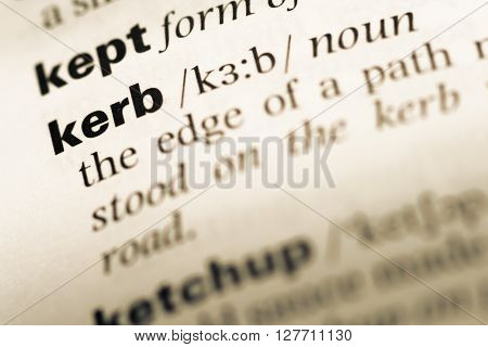 Close Up Of Old English Dictionary Page With Word Kerb.
