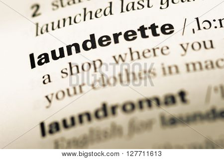 Close Up Of Old English Dictionary Page With Word Launderette.