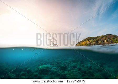 Sailing boat anchored in a tropical sea. Split shot with underwater view of the coral reef